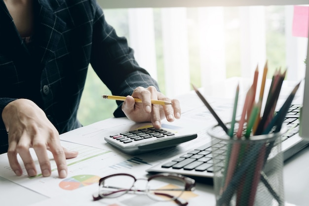 Close up of businessman or accountant hand holding pencil working on calculator