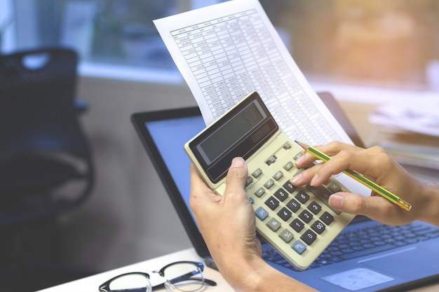 Close up of businessman or accountant hands holding calculator pencil and financial report