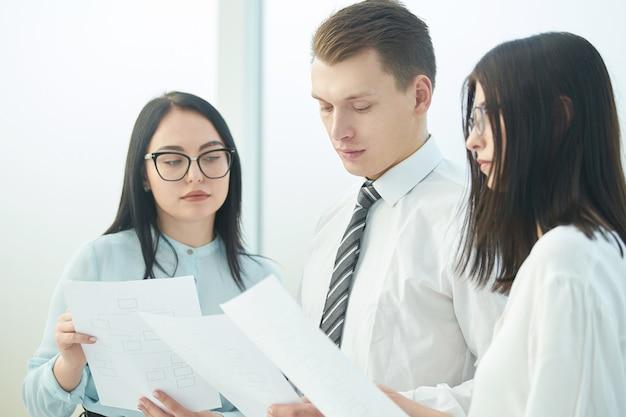 Крупным планом бизнесмен и бизнес-леди обсуждают деловые документы