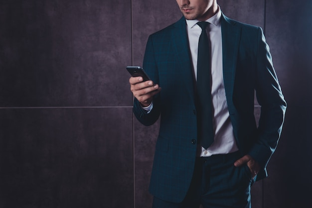 Close up of businessman in black suit using smartphone on gray space