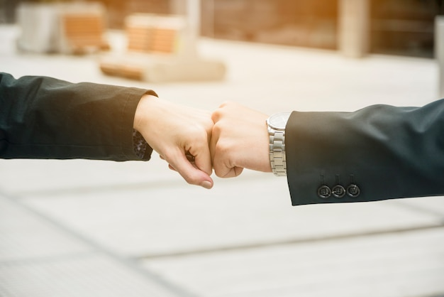 Close-up of businessman and businesswoman making a fist bump