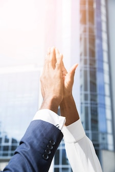 Close-up of businessman and businesswoman's hand giving high five