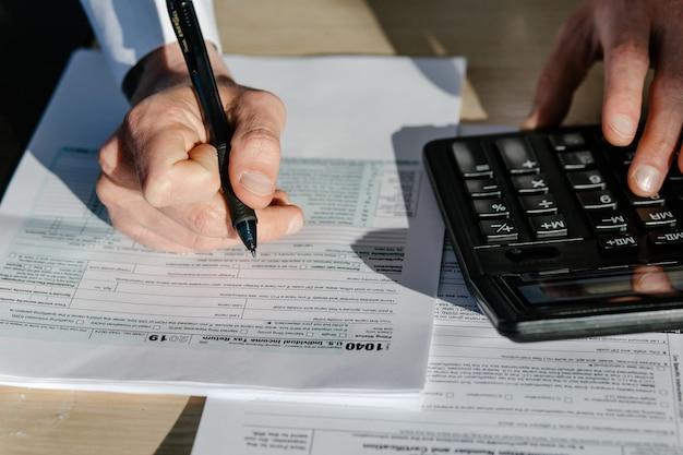 Крупным планом бизнесмен рассчитать индивидуальную налоговую декларацию в современном офисе. бизнесмен с помощью калькулятора.