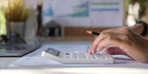 Close-up of a businessman calculating invoice using calculator at workplace