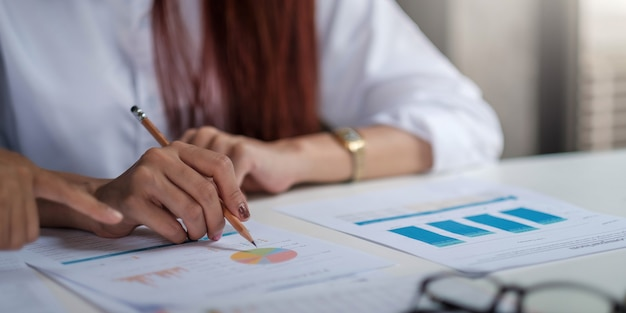 Close-up of businessman checking financial graphs showing the results of their successful teamwork at the office.
