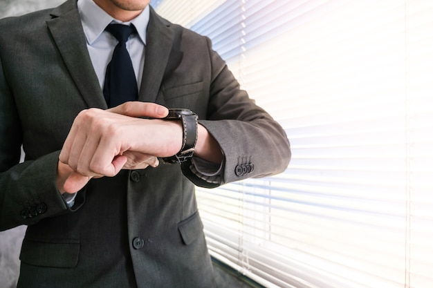 Close up of businessman checking time on his wrist watch while standing at a window in an office