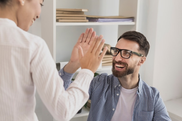 Close-up of businessman giving high five to woman