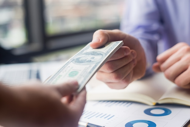 Close up businessman giving money his partner in office, business concept