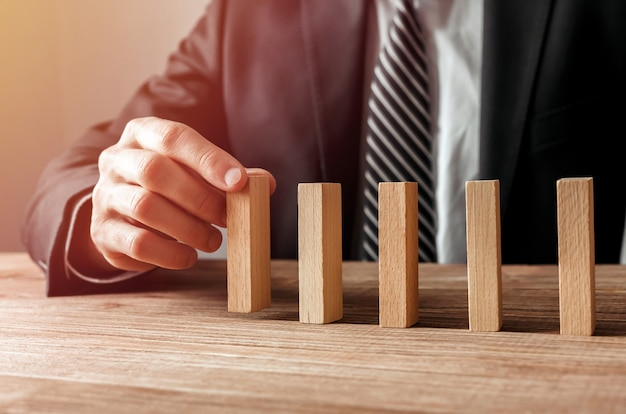 Close up of businessman hand gambling placing wooden block on a line of domino.risk and business strategy concept.