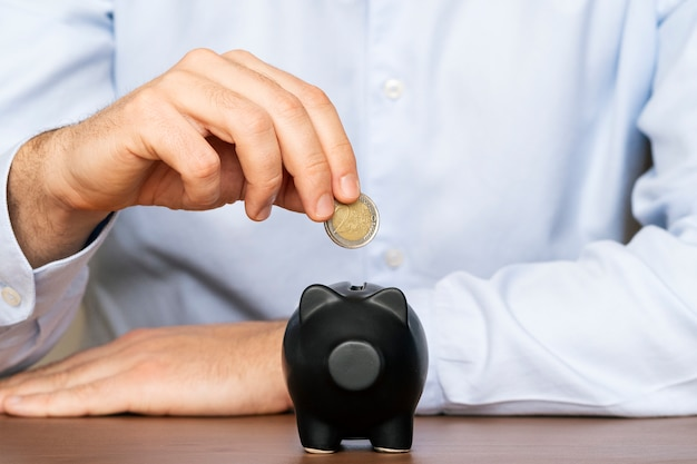 Close up of businessman hand putting coin into piggy bank. saving money concept