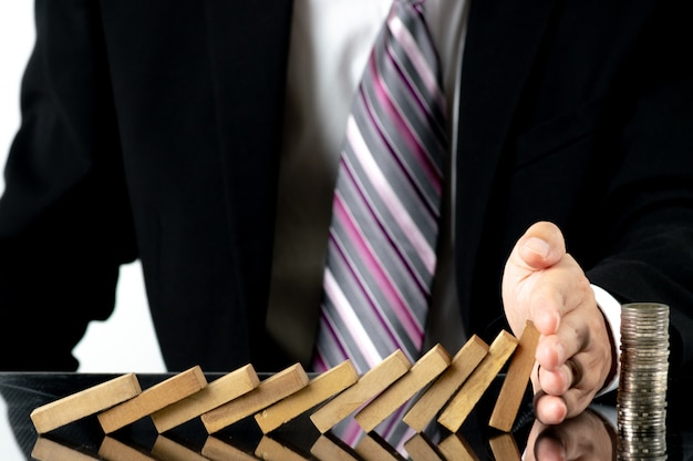 Close-up businessman hand stopping wooden blocks from falling on stacked coins over desk