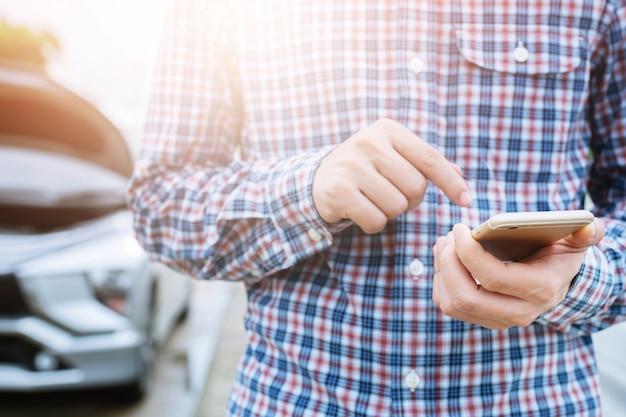 모바일 스마트 전화를 사용하여 사업가 손을 닫습니다. 자동차 정비사가 도움을 요청합니다.