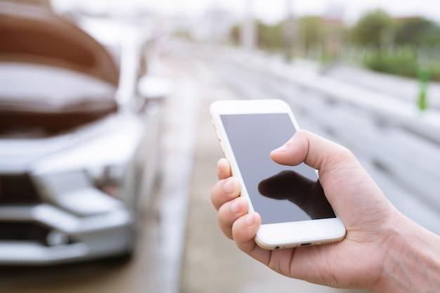 모바일 스마트 전화를 사용하여 사업가 손을 닫습니다. 자동차 정비사에게 도움을 요청하십시오.