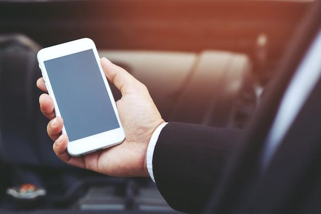 모바일 스마트 전화를 사용하여 사업가 손을 닫습니다 자동차 정비사