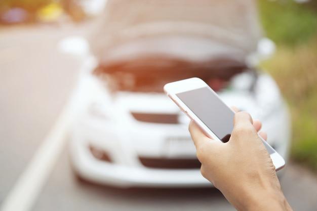 Закройте вверх руки бизнесмена, используя мобильный смартфон, чтобы вызвать автомеханика, чтобы попросить о помощи