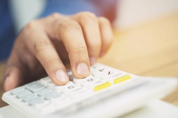 電卓を使用してビジネスマンの手をクローズアップし、メモを数えるノートに書くオフィスで財務を行う際の会計。貯蓄財政の概念。