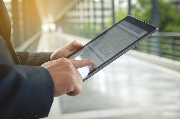 Close up businessman hand using tablet and pointing on summary report at office.