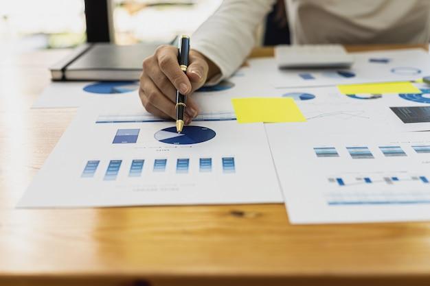 펜을 들고 회사 재무 문서의 막대 차트를 가리키는 클로즈업 사업가는 회사 성장 방법을 계획하기 위해 과거 재무 데이터를 분석하고 있습니다. 금융 개념입니다.