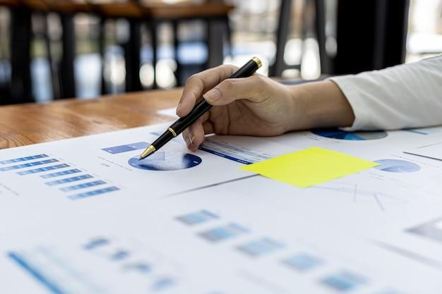 Крупный план бизнесмена, держащего ручку и указывающего на столбчатую диаграмму финансового документа компании, он анализирует исторические финансовые данные, чтобы спланировать, как развивать компанию. финансовая концепция.