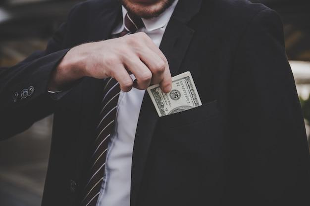 Close up of businessman holding dollar bills on his pocket.