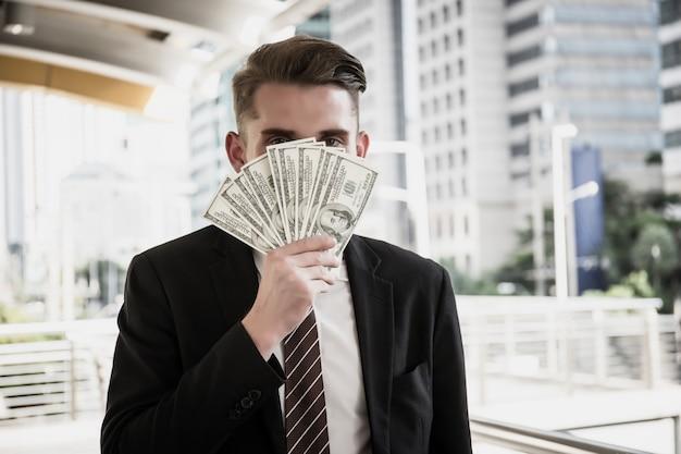 Close up of businessman holding dollar bills.