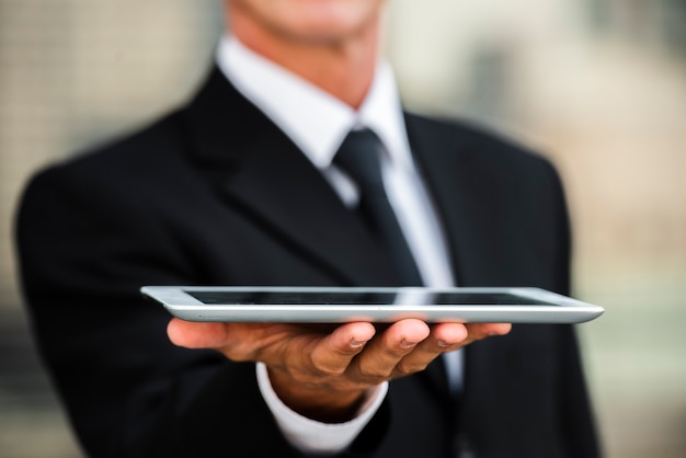 Close-up businessman holding tablet in hand