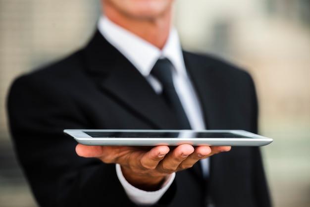 Крупным планом бизнесмен, держа в руке планшет