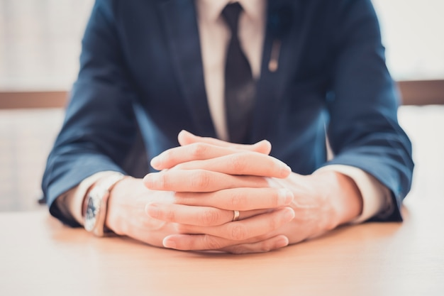 Close-up of businessman keeping fingers crossed on the table