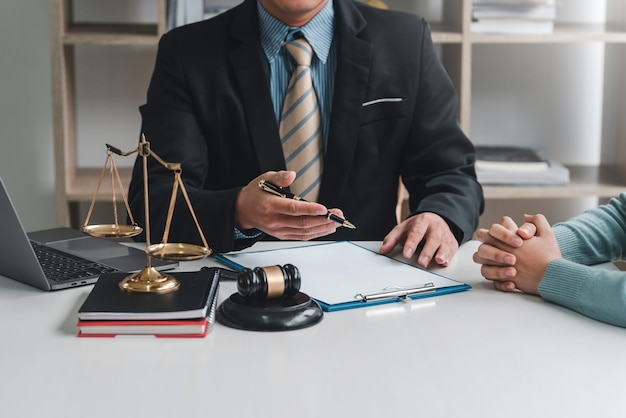 Close-up of businessman lawyer and client sitting at the office negotiating together using document.