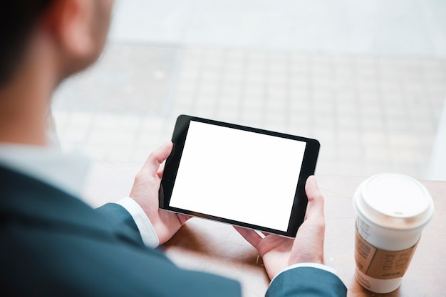 Close-up of a businessman looking at digital tablet with white screen display in caf�