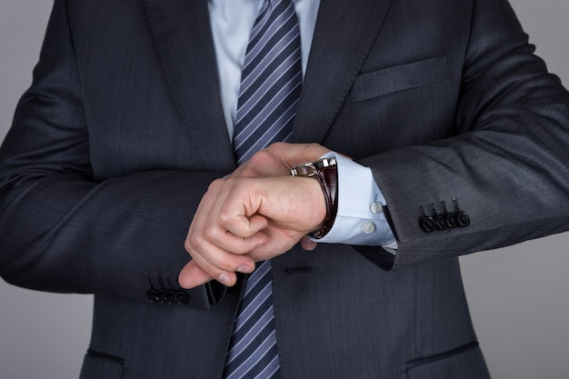 Close up businessman looking at his wristwatch checking the time