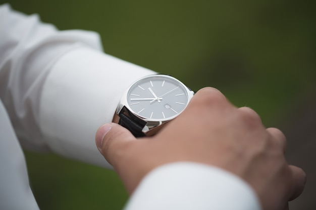 Close up of businessman looking at watch on his hand outdoors