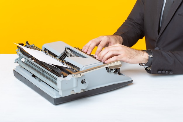 Close up of businessman or manager in formal suit typing text on a typewriter on a yellow background