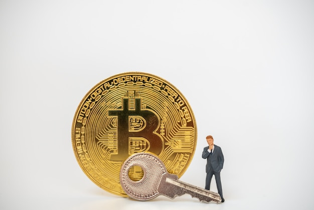 Close up of businessman miniature figure people standing with gold bitcoin coins and silver key
