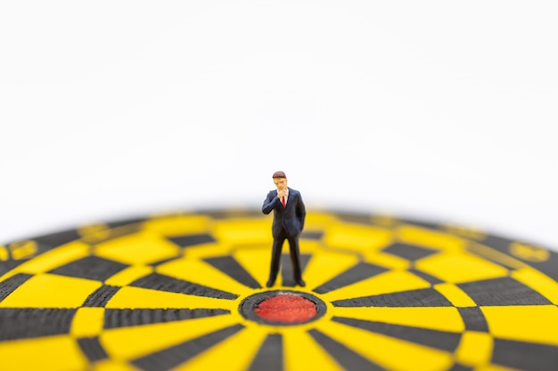Close up of businessman miniature figure standing close to center of  dart board