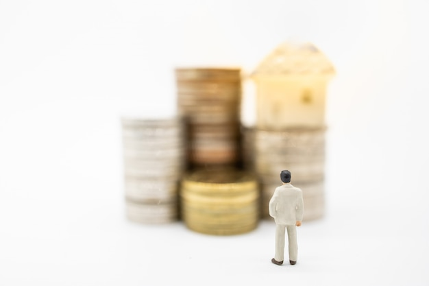 Close up of businessman miniature figure standing and looking to stack of coins and mini house toy on top.