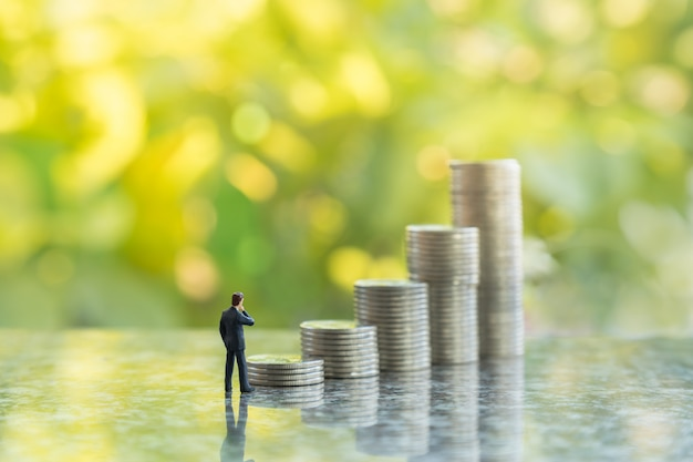Close up of businessman miniature figures standing and looking tp stack of coins with bokeh green leaf nature
