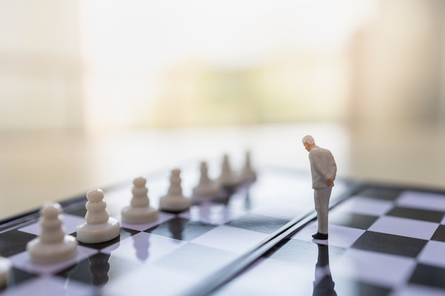 Close up of businessman miniature people figure standing on chessboard with pawn chess pieces and copy space.