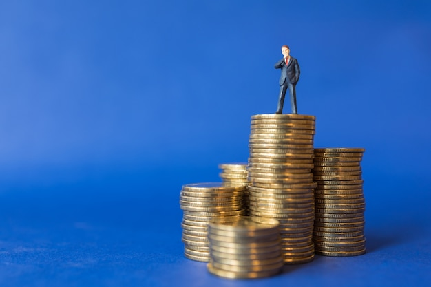 Close up of businessman miniature people figure standing on top of stack of gold coins