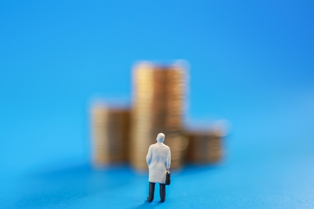 Close up of businessman miniature people figure with handbag standing and looking to stack of gold coins on blue background