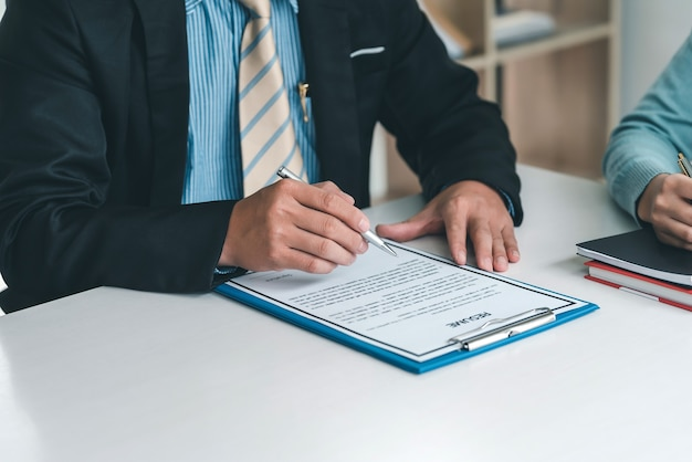 Close-up of businessman owner hand holding pen to check resume at office.