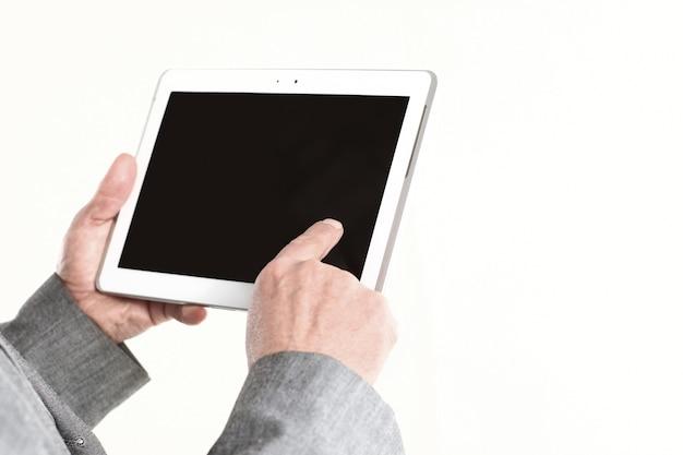 クローズアップ。ビジネスマンは、空白の画面のタブレットに指を指しています。白い背景で隔離。