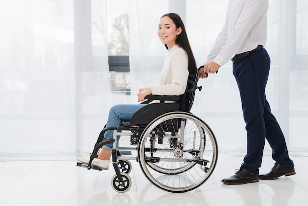 Close-up of a businessman pushing the disabled woman sitting on wheelchair