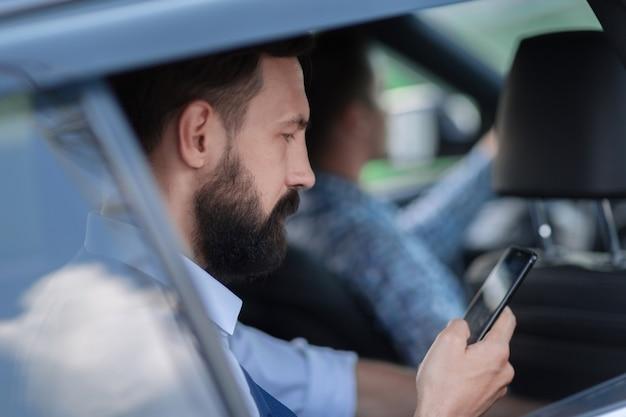 Крупным планом. бизнесмен, читающий sms на своем смартфоне. люди и технологии