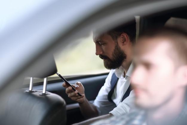 Закройте вверх. бизнесмен, читающий sms на своем смартфоне, сидя в машине. люди и технологии