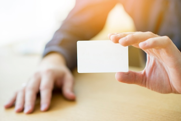 Close-up of a businessman's hand holding blank white card