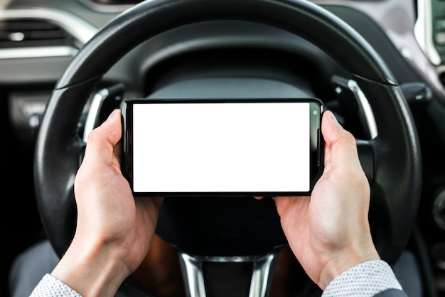 Close-up of a businessman's hand holding smartphone in front of steering wheel