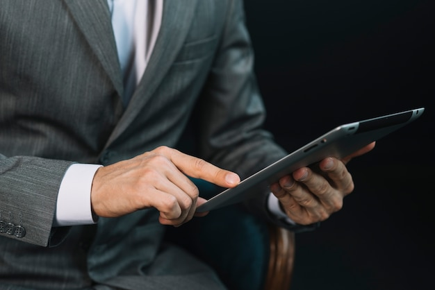 Close-up of a businessman's hand touching the digital tablet screen