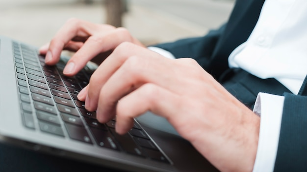Close-up of businessman's hand typing on laptop