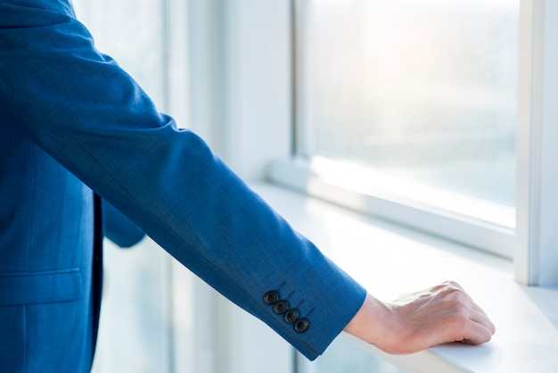 Close-up of a businessman's hand on windowsill